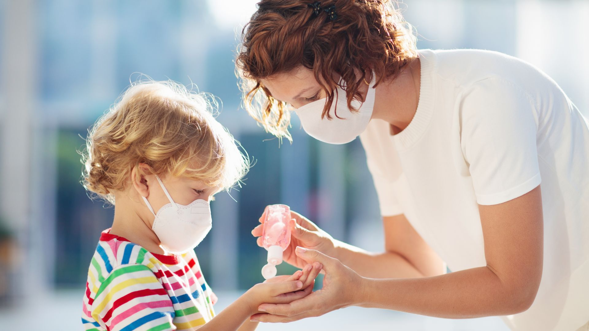 Mother and child with face mask and hand sanitiser