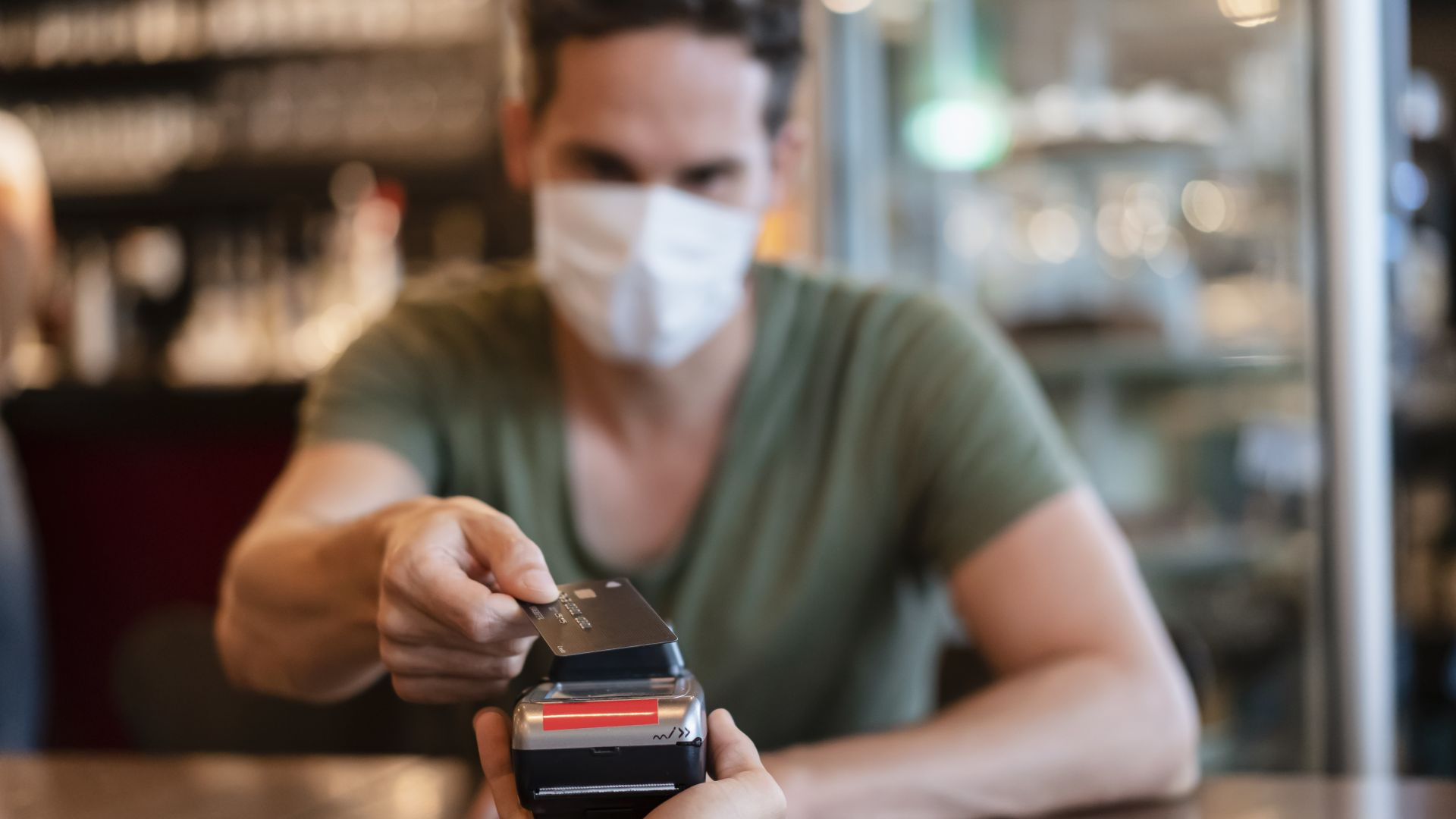 Man in protective mask paying with credit card in restaurant